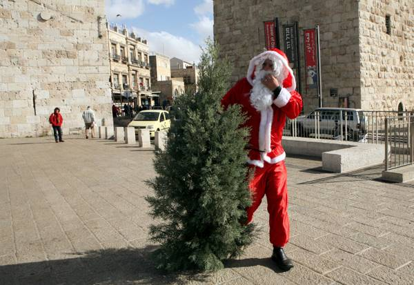 A Santa Claus carries a way a Christmas tree at the Jaffa Gate in Jerusalem's Old City [ARCHIVE MATERIAL ]