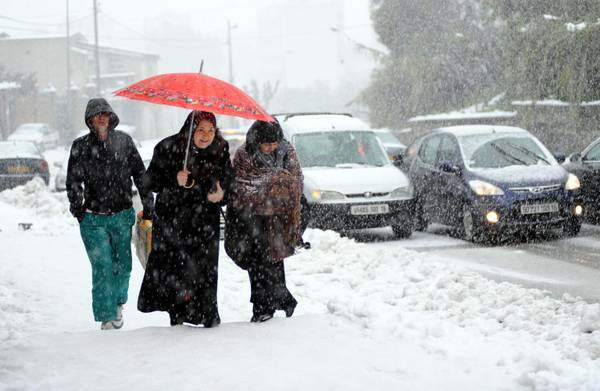Algerians make their way in snow in Algiers, Algeria