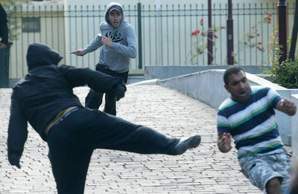 Greek racists, one of them (C) holding a knife, attacking a migrant (R) in the center of Athens (archive photo)