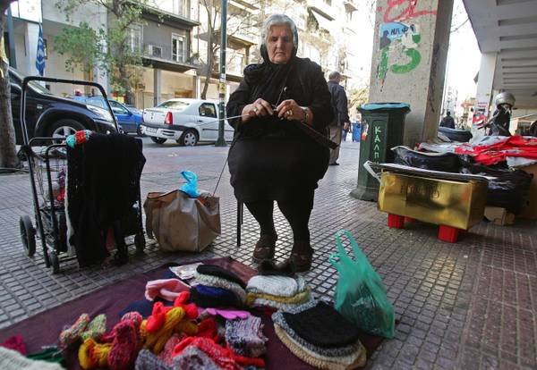 A woman knitting caps on a pavement in central Athens [ARCHIVE MATERIAL 20111212 ]