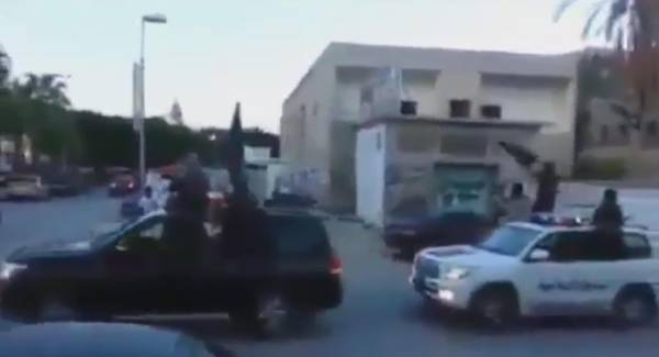 Ansar al Sharia militants in Derna aboard armed pickup trucks waving ISIS flags and hailing al Baghdadi in a shot from a video