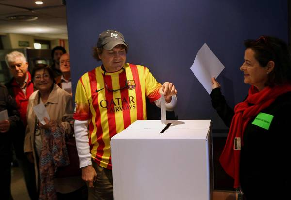 A man dressed with the Barcelona FC t-shirt votes during the non binding 'referendum' for  independance at a voting center in Barcelona, Spain
