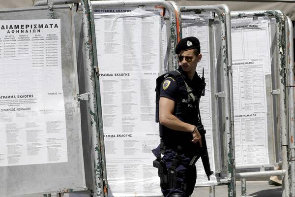 A police officer stands guard near banners with lists of the polling stations in the center of Athens, Greece