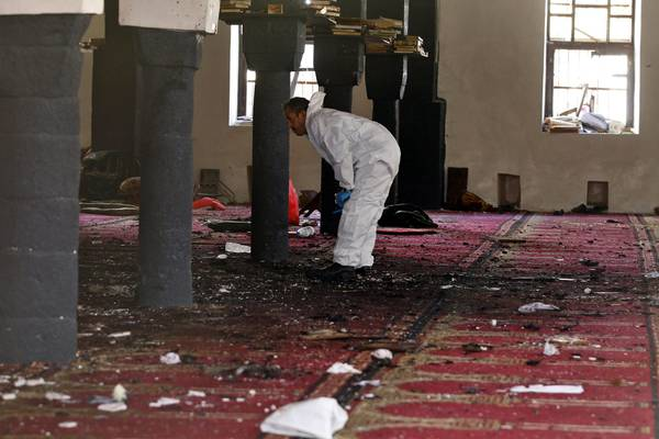 A forensic expert inspects the scene of a suicide attack targeting the al-Hashahush mosque in Sanaa, Yemen.