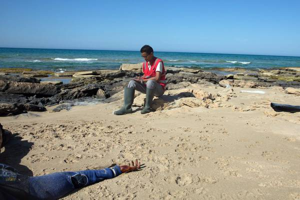 The body of a drowned migrant (L) off the shore of Gasr Garabulli, in  the eastern city of Tripoli