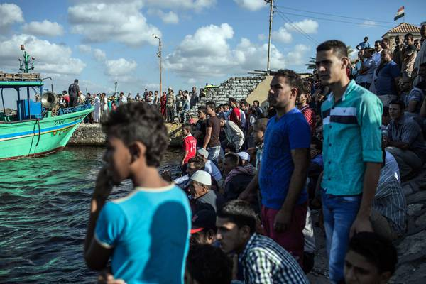 Egyptians wait on shore as a coast guard boat arrives carrying the bodies of migrants from a  boat that capsized  with hundreds of migrants on board